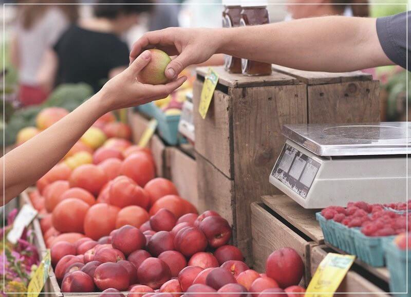 девочка покупает яблоко